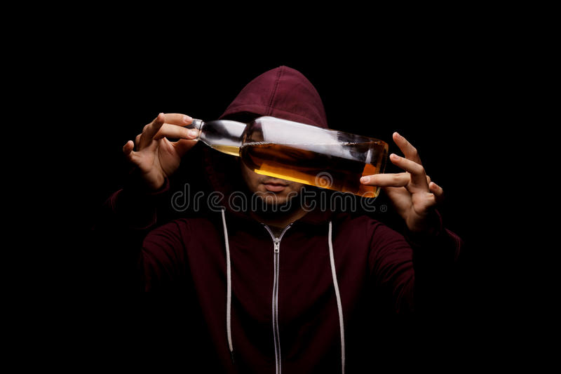 An youth man with a bottle full of light brown liquor on a black background. Alcoholic, dependent and bad concept. stock photo