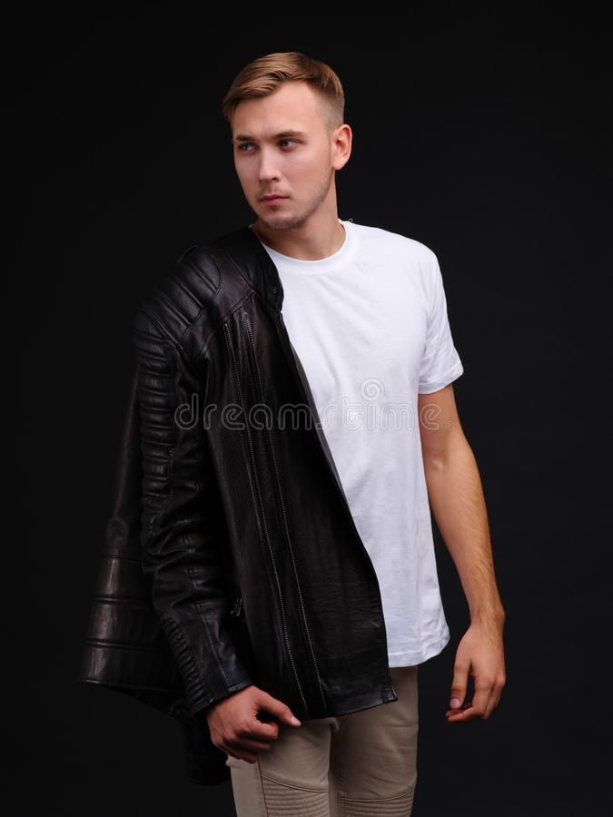 The guy in T-shirt and a jacket on one hand, looks away with a serious look and holds his hand in pocket. stock photo