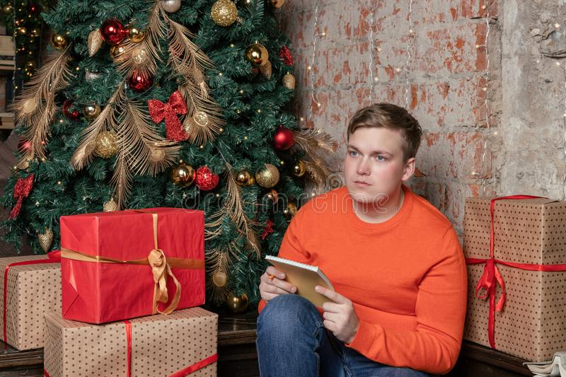 Handsome guy is writing a letter to Santa sitting under the tree surrounded by boxes of gifts. Christmas and gifts stock images