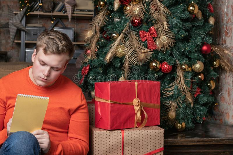 Handsome guy is writing a letter to Santa sitting under the tree surrounded by boxes of gifts. Christmas and gifts royalty free stock photos