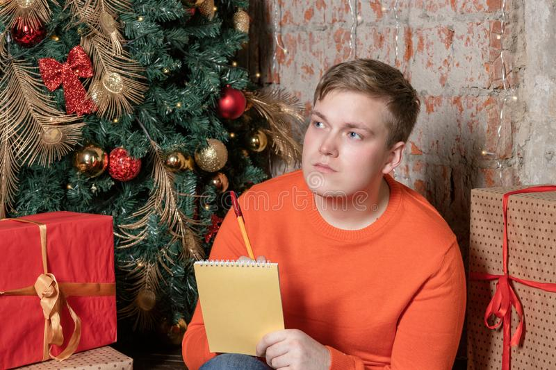 Handsome guy is writing a letter to Santa sitting under the tree surrounded by boxes of gifts. Christmas and gifts stock photos