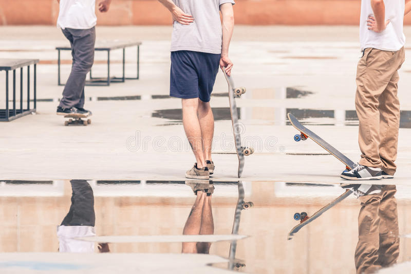 Handsome guys with skateboard at freestyle park outdoors. With beautiful reflection royalty free stock photos