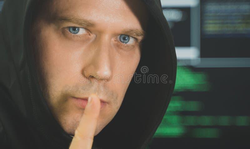 Handsome hacker in black hoodie. royalty free stock photos