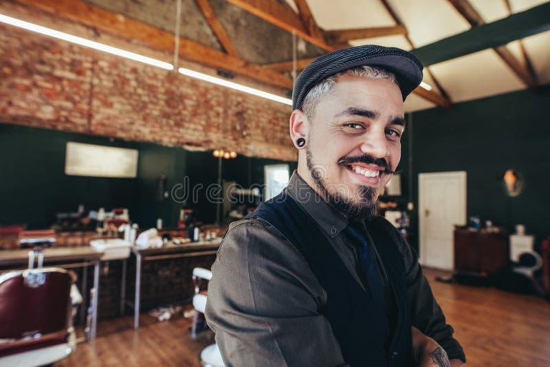 Handsome hairdresser smiling at barbershop royalty free stock images