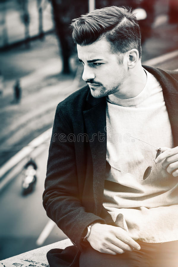 Handsome hairstyle young man city outdoors. Black and white stock photo