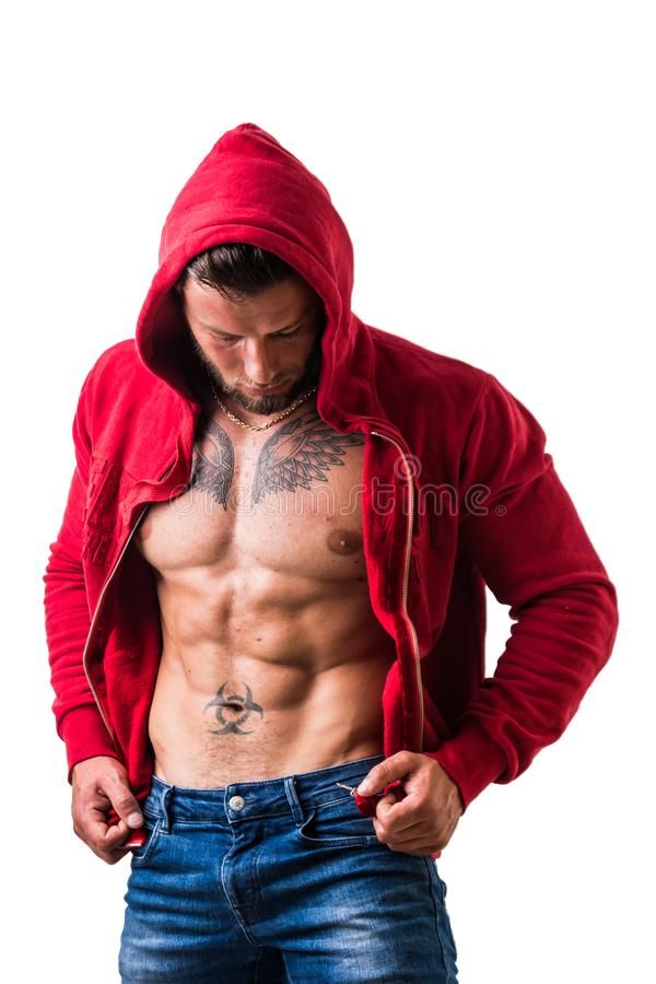 Handsome half-naked muscular man standing, isolated. Handsome muscular man with sweater open on naked torso, standing, isolated on white background in studio royalty free stock photography