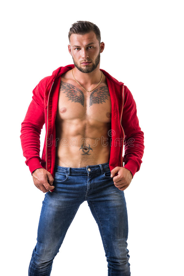 Handsome half-naked muscular man standing, isolated. Handsome muscular man with sweater open on naked torso, standing, isolated on white background in studio royalty free stock images