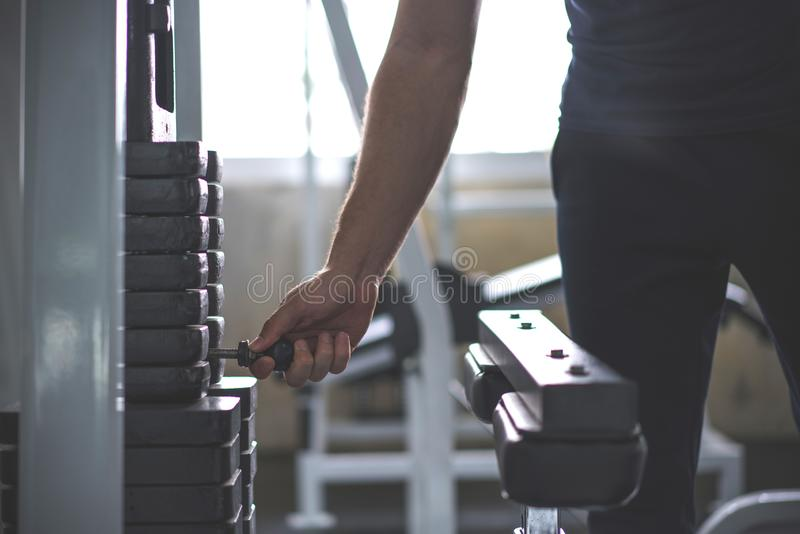 Handsome hand change weight on Iron heavy plates stacked of weight machine in gym stock photos