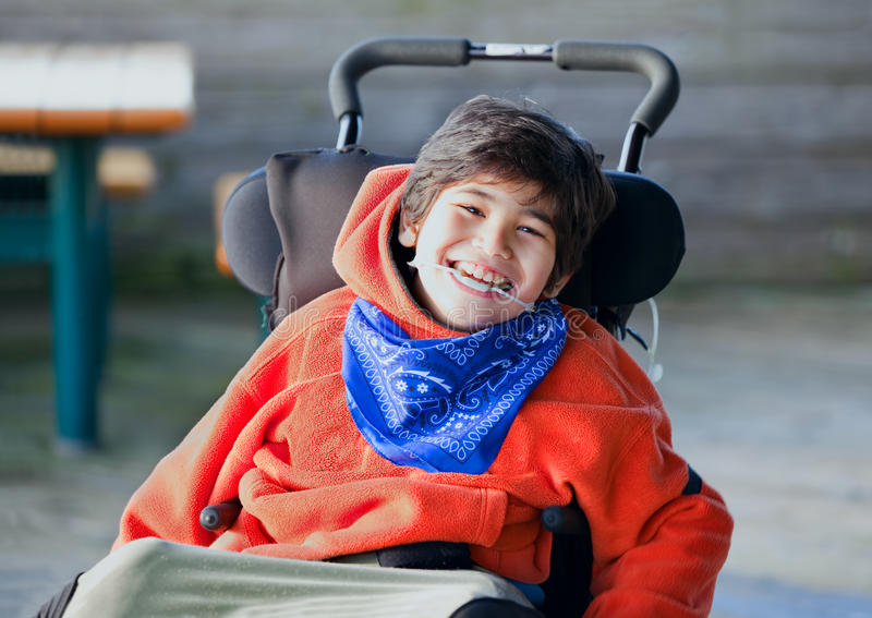 Handsome, happy biracial eight year old boy smiling in wheelchair outdoors royalty free stock photos