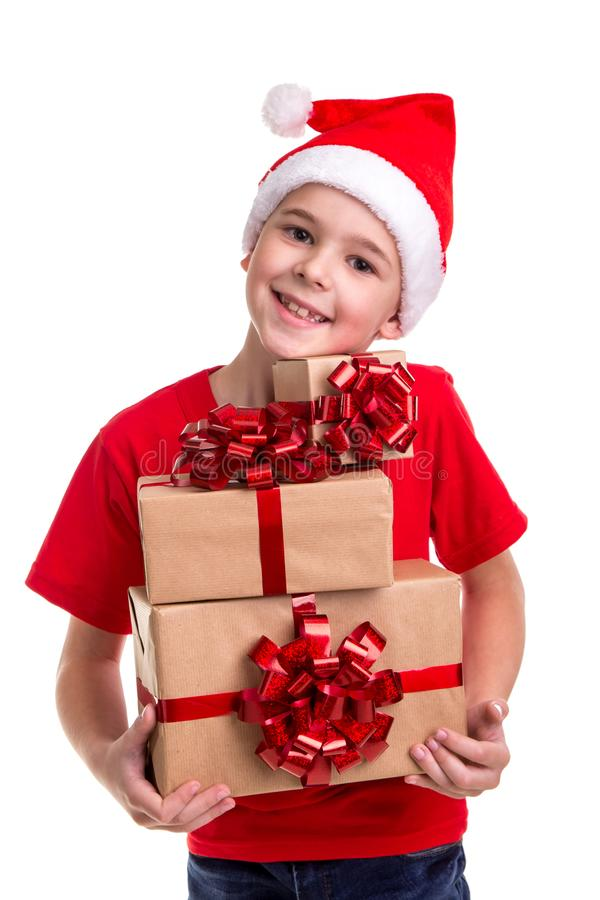 Handsome happy boy, santa hat on his head, with bunch of the gift boxes in the hands. Concept: christmas or Happy New royalty free stock photos