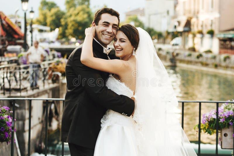 Handsome happy bride and beautiful sensual groom at romantic bridge in france closeup royalty free stock photos