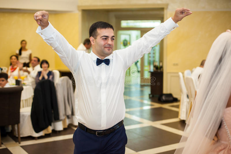 Handsome happy groom in white shirt having fun during first dance with bride at reception stock photos