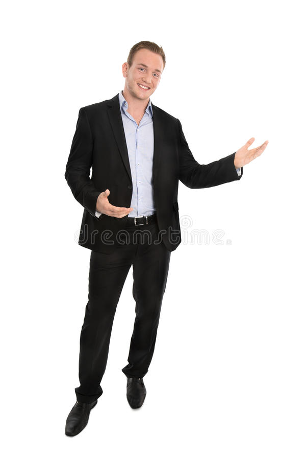 Handsome happy isolated young businessman presenting with hands. royalty free stock photos