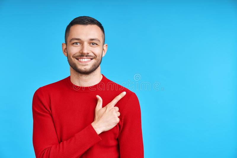 Handsome happy man pointing his finger showing empty copy space royalty free stock images