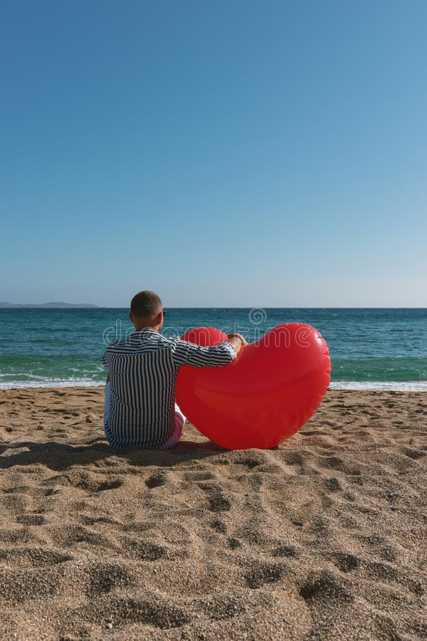 Handsome happy man sitting with big heart balloon on the beach. Summer love concept royalty free stock images