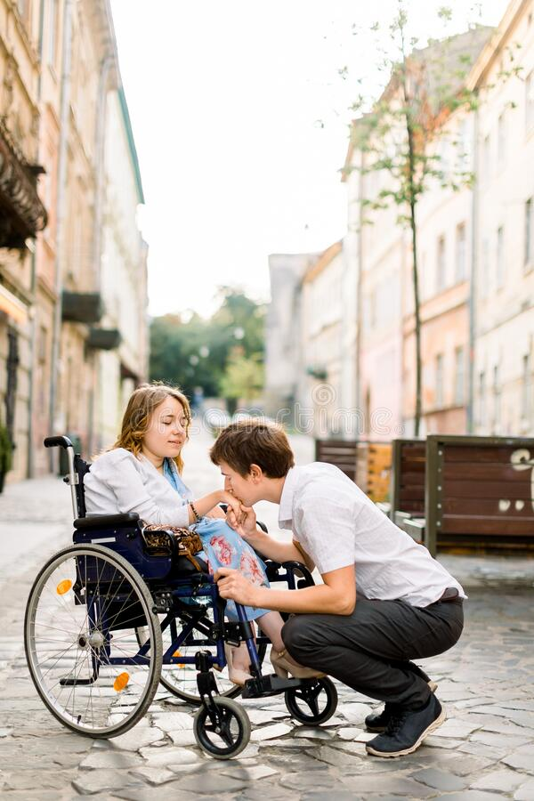 Handsome happy man smiling and holding hand of his beautiful beloved blond handicapped woman in wheelchair while walking. Handsome happy men smiling and holding royalty free stock image