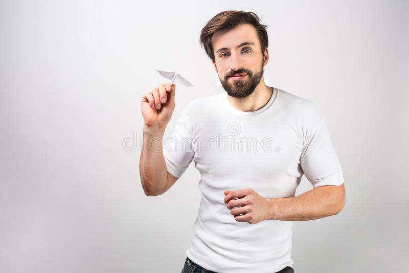 Handsome and happy man in white shirt is standing near the wall and holding a paper airplane. He is ready to launch it stock photo