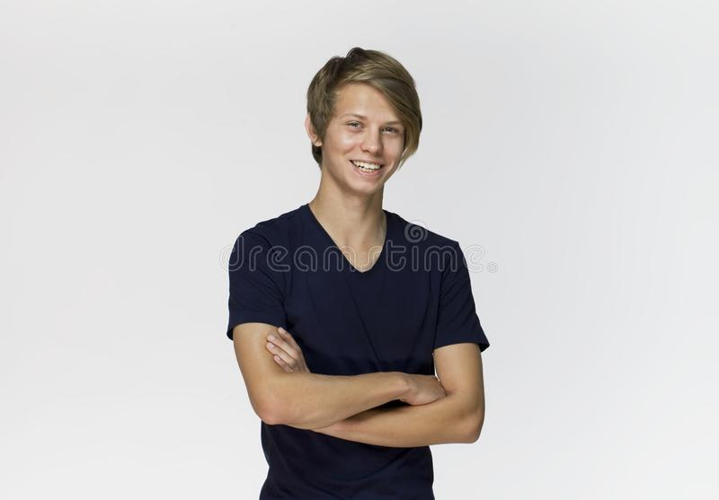 Handsome happy smiling young man wearing black t-shirt with crossed arms studio portrait against white wall stock photo
