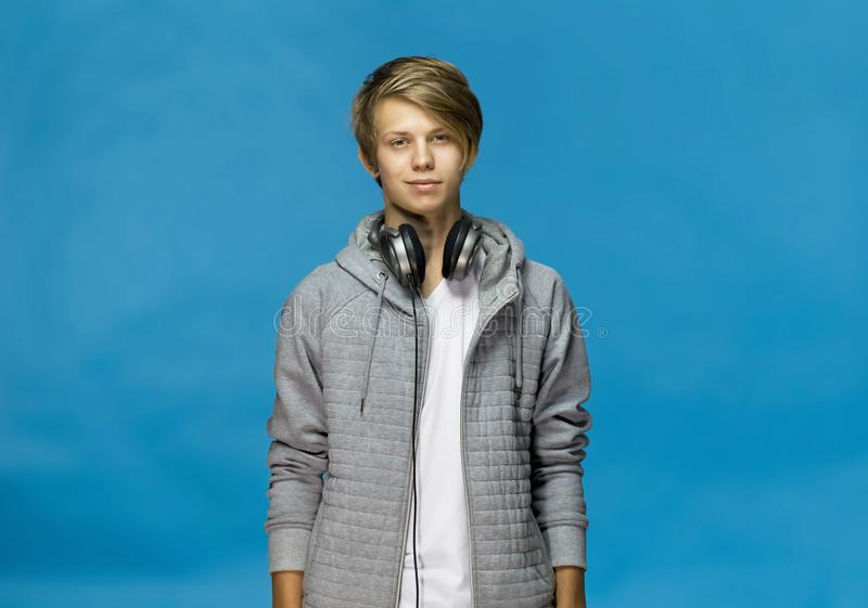 Handsome happy smiling young man wearing gray blouse with headphones studio portrait against blue wall stock photography