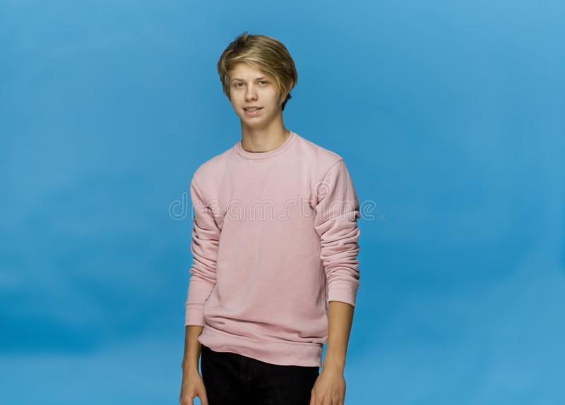 Happy blonde teenager smiling and posing in pink blouse against blue background royalty free stock images