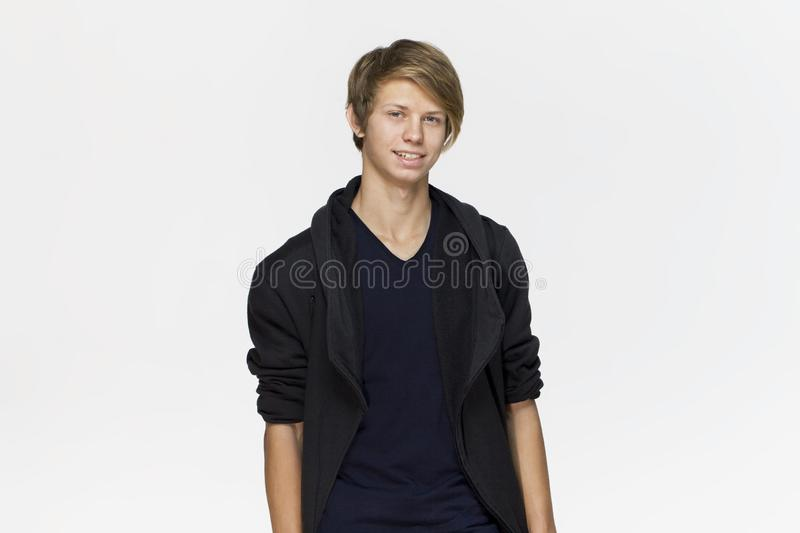 Handsome happy young man wearing black blouse studio portrait against white wall stock images