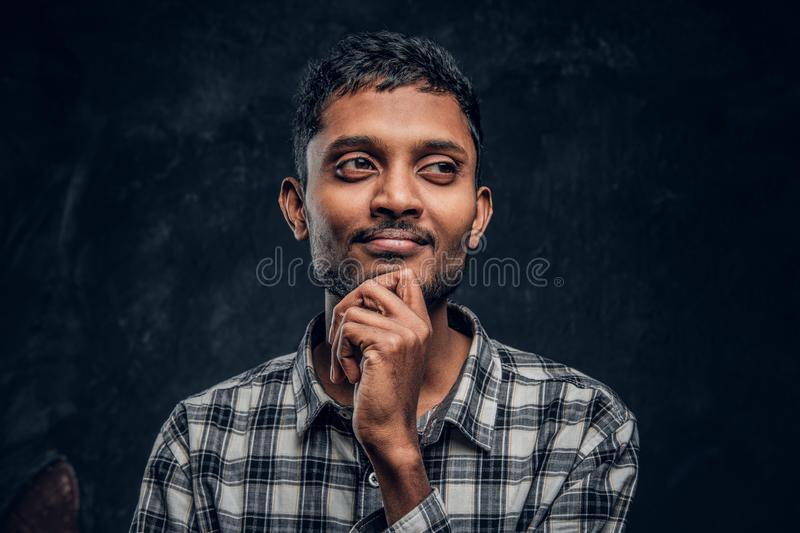 Handsome hindu guy dreams and put his arm under the chin. In the studio on a black background stock images