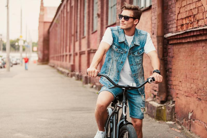 Handsome hipster enjoying city ride by bicycle. stock images