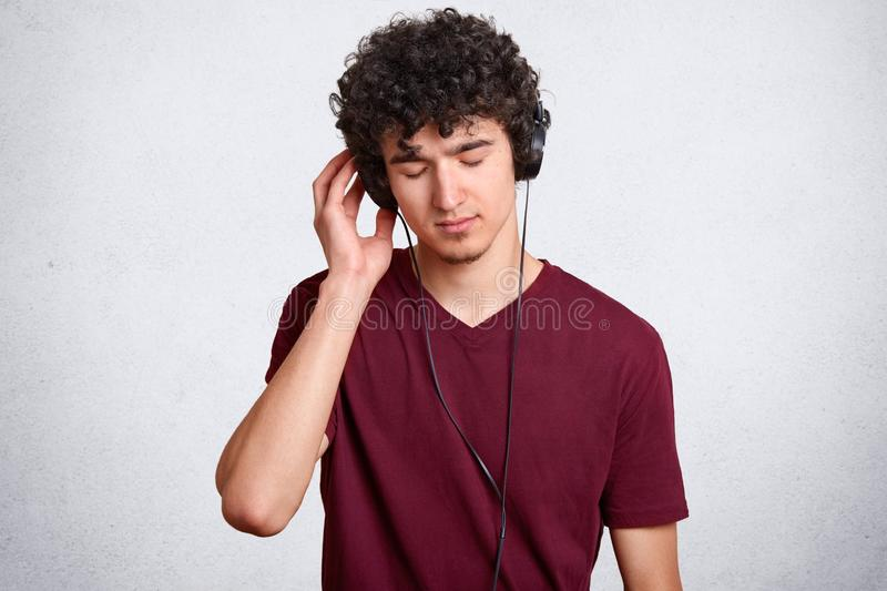 Handsome hipster guy in casual clothes with big headphones listening music with closed eyes and enjoying, spending his free time, stock photography