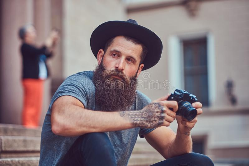 A handsome hipster male with a stylish beard and tattoo on his arms dressed in casual clothes and hat holds a camera royalty free stock image