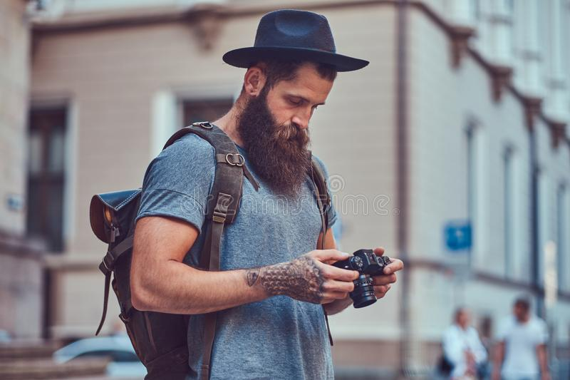 A handsome hipster male with a stylish beard and tattoo on his arms dressed in casual clothes, using a photo camera. stock images