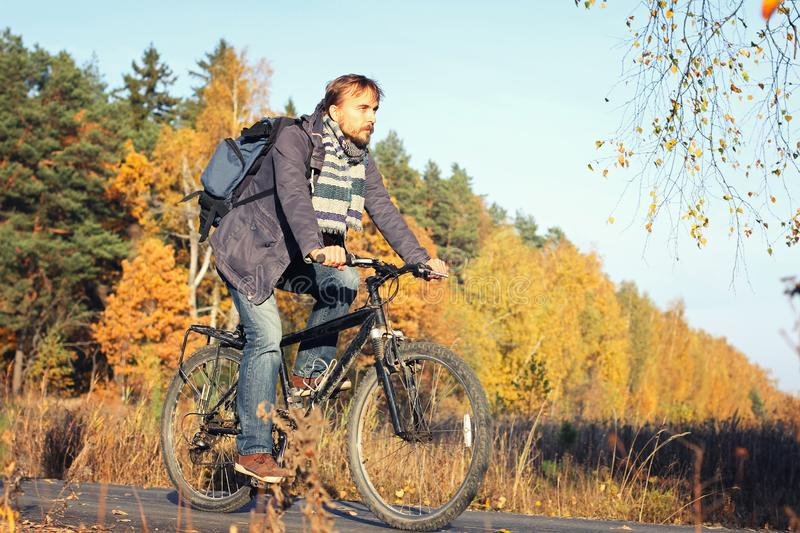 Handsome hipster man in casual wear with backpack riding bicycle in autumn park or forest. Discovery beautiful fall season stock images
