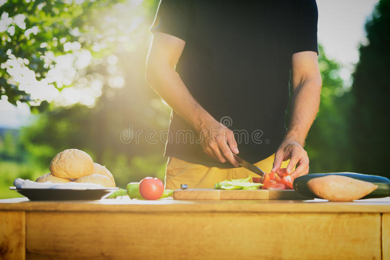 Handsome hipster man preparing food, bbq summer garden food royalty free stock photos