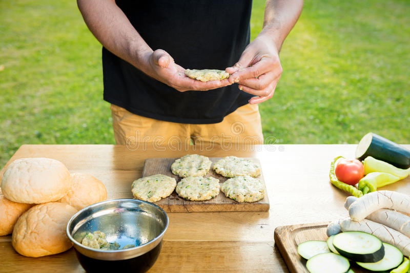 Handsome hipster man preparing meat and zucchini burgers, bbq summer garden food royalty free stock photography
