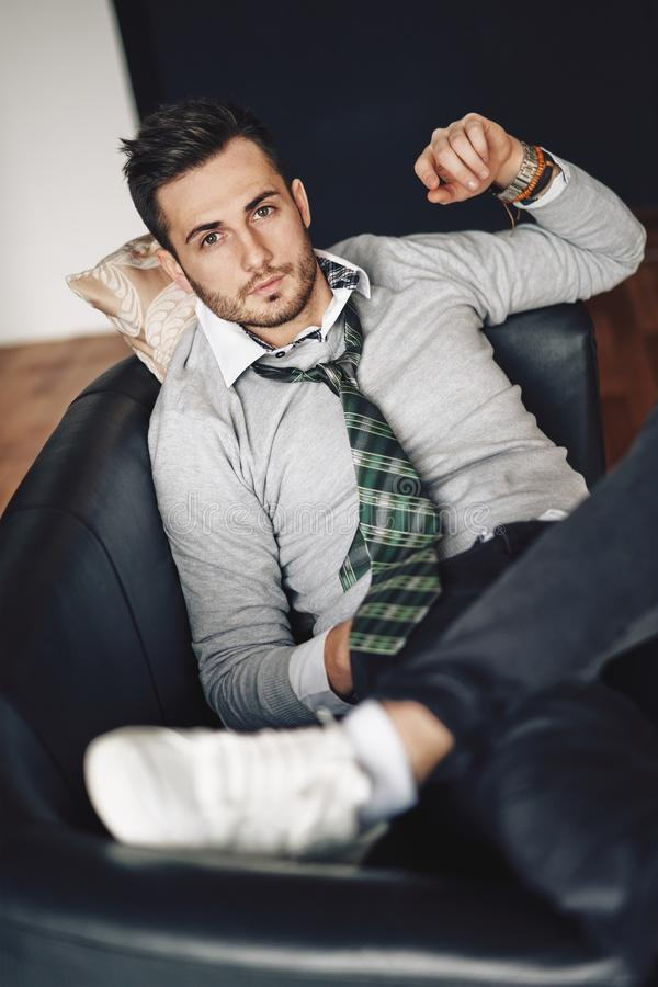 Handsome hipster man relaxing in sofa royalty free stock image