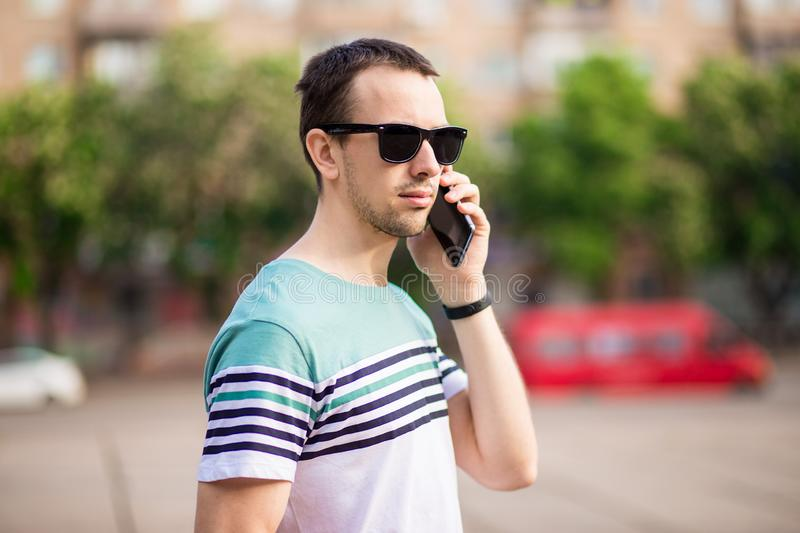 Handsome hipster modern businessman with beard walking and calling on mobile phone royalty free stock image