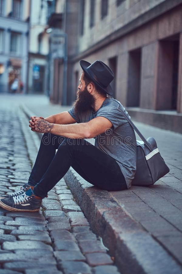 A handsome hipster traveler with a stylish beard and tattoo on his arms dressed in casual clothes with a bag, sits on royalty free stock photos