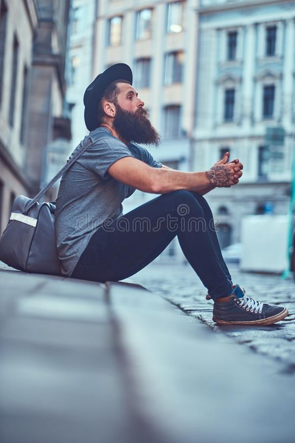 A handsome hipster traveler with a stylish beard and tattoo on his arms dressed in casual clothes with a bag, sits on royalty free stock photo