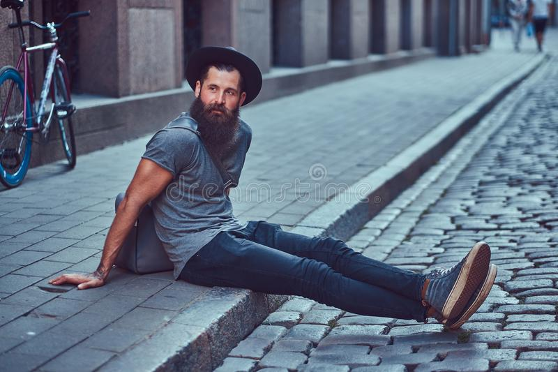 A handsome hipster traveler with a stylish beard and tattoo on his arms dressed in casual clothes with a bag, sits on stock image