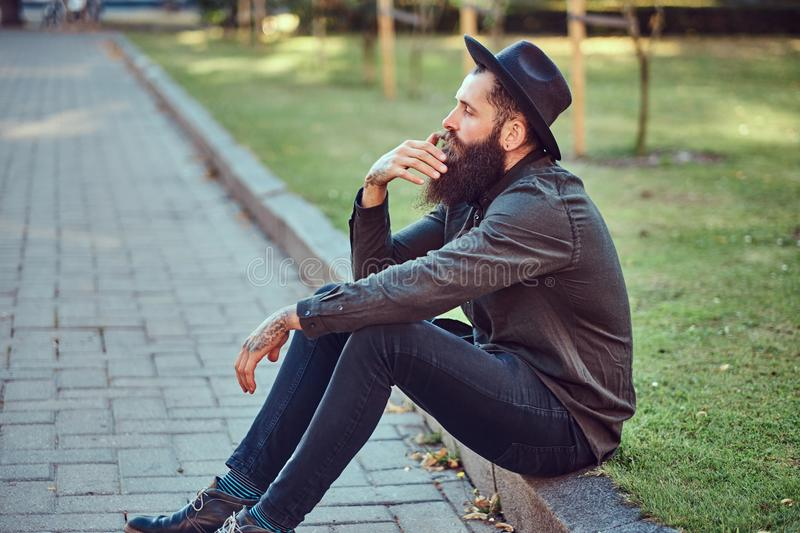 A handsome hipster traveler with a stylish beard and tattoo on his arms dressed in casual clothes and hat, sitting on royalty free stock photography