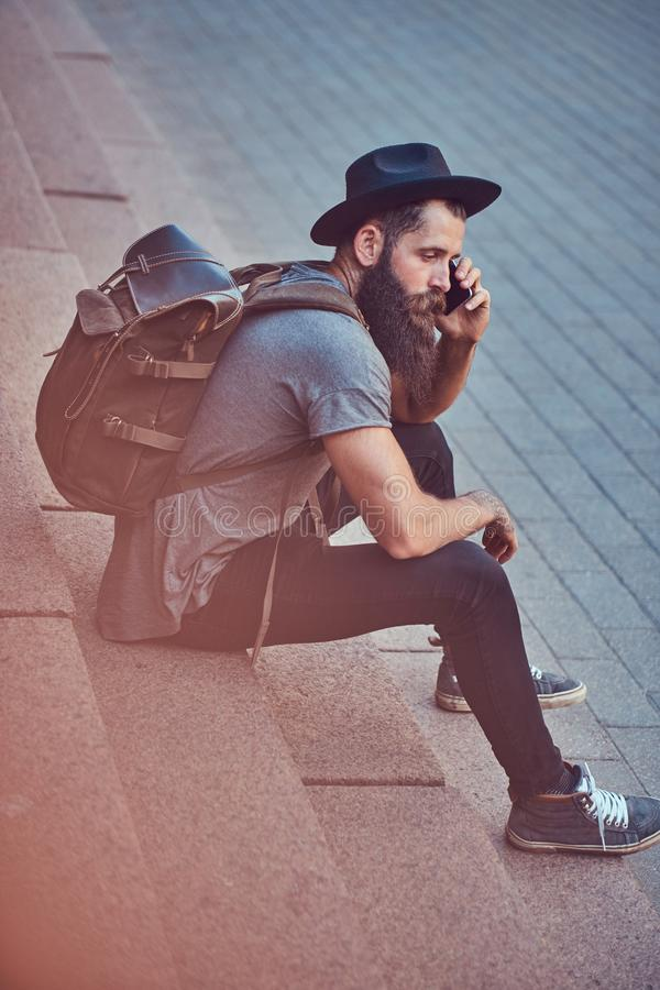 A handsome hipster traveler with a stylish beard and tattoo on his arms dressed in casual clothes, sitting on the steps stock photos