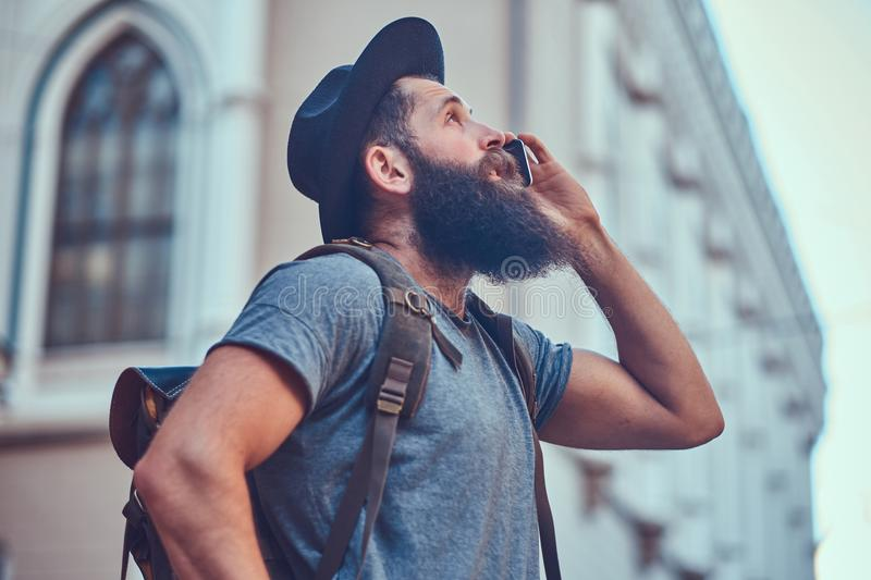A handsome hipster traveler with a stylish beard and tattoo on his arms dressed in casual clothes, standing on the royalty free stock photo