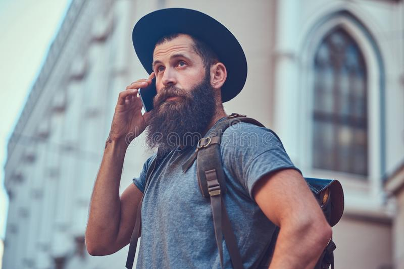A handsome hipster traveler with a stylish beard and tattoo on his arms dressed in casual clothes, standing on the stock image