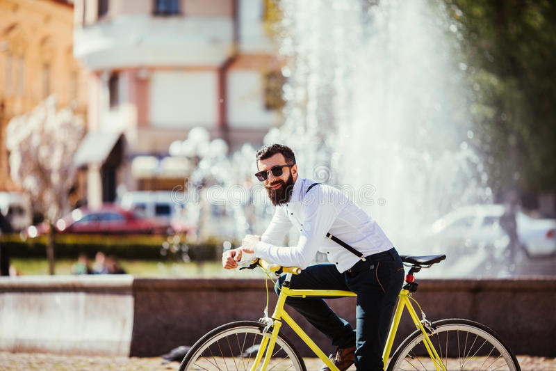 Handsome hipster young bearded man looking at camera while sitting on his bicycle outdoors near fountains royalty free stock photos