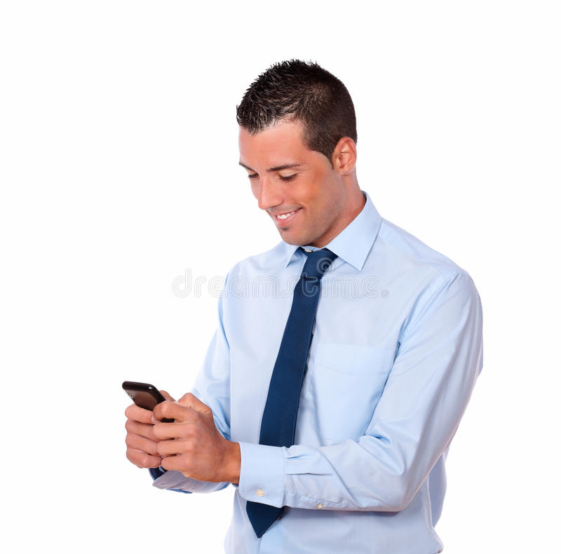 Handsome hispanic guy sending a message. Portrait of a handsome hispanic guy sending a message with his mobile on isolated background stock images