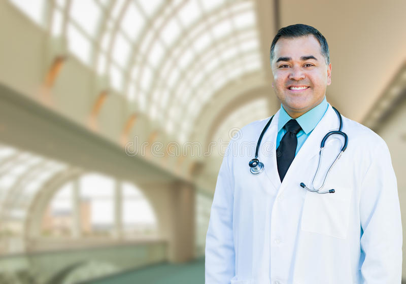 Handsome Hispanic Male Doctor or Nurse Inside Hospital Building. Handsome Hispanic Male Doctor or Nurse Standing Inside Hospital Building royalty free stock photography