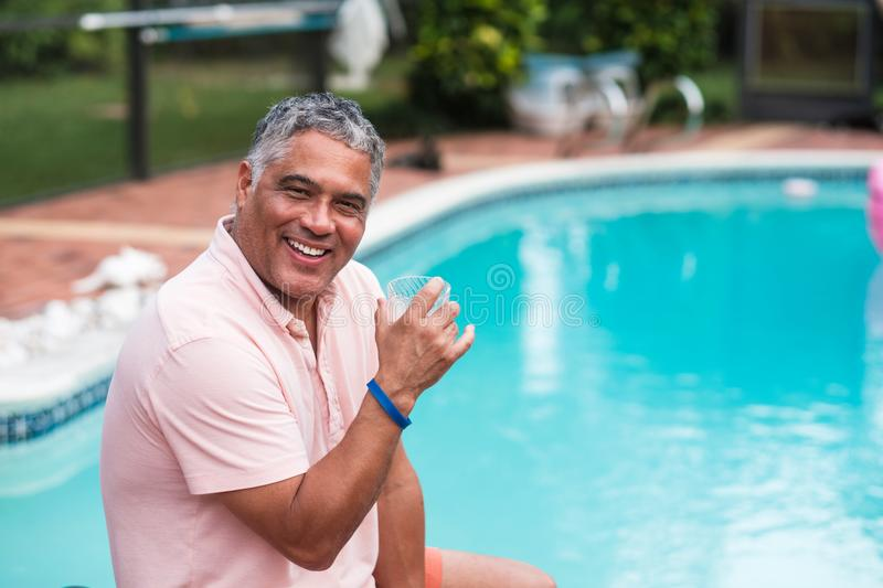 Handsome Hispanic Man Outdoors. Handsome middle age hispanic man outdoor lifestyle by a swimming pool in a home setting stock images