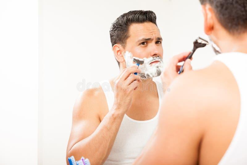 Handsome Hispanic man shaving his beard royalty free stock photo