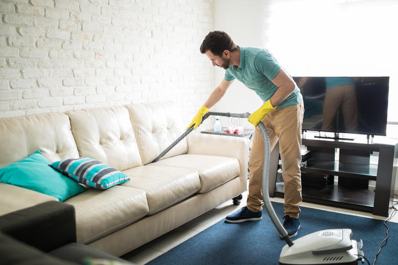 Latin man cleaning the sofa stock images