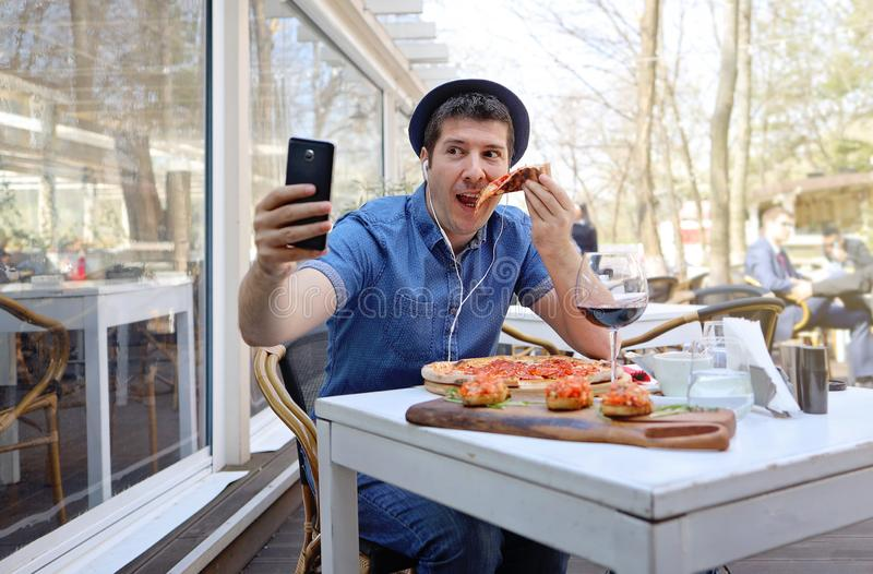 Handsome hunger man eating pizza and showing off in a video conference with his friends royalty free stock images