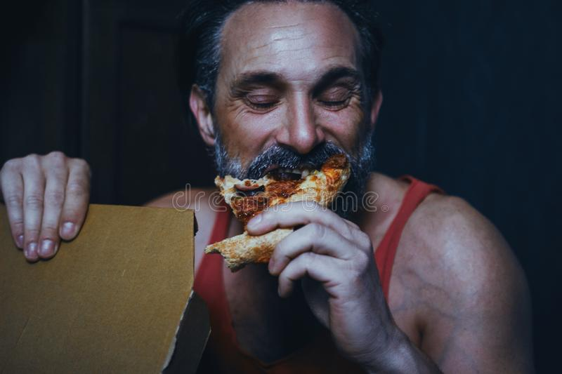 Handsome hungry man is eating pizza. stock images